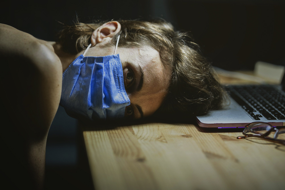 Photograph of a person wearing a medical mask resting their head on a desk in front of a computer.