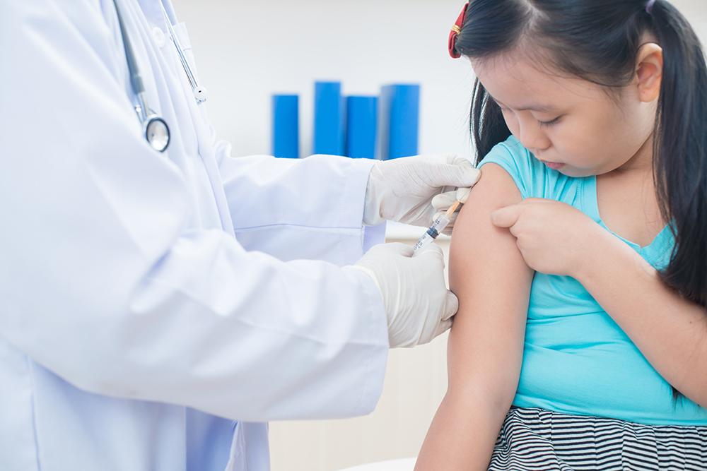 Photograph of a young girl receiving an immunization.