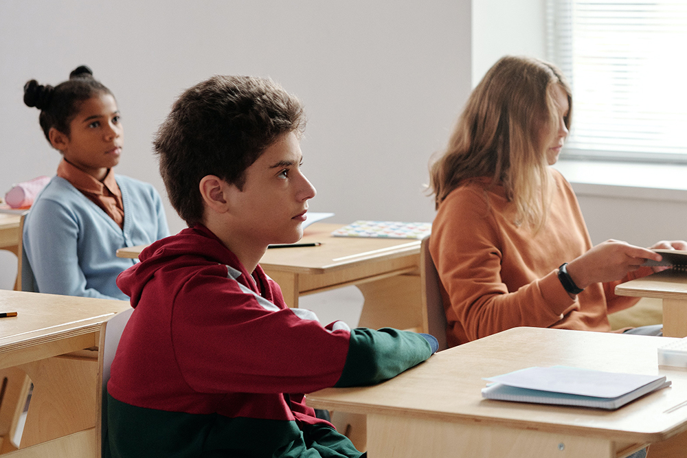 Photograph of young teen students at desks in a classroom.