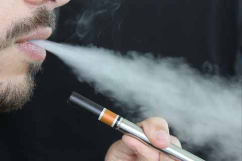 Photo of the lower quarter of a man's face blowing out smoke, while he holds a vape pen.