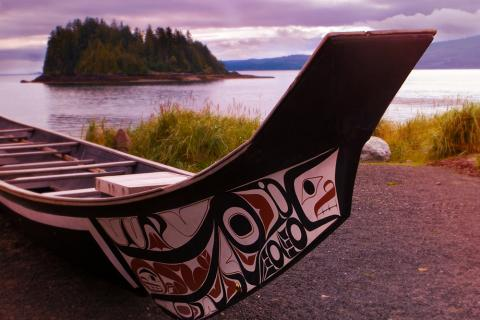 A native canoe on a beach near coastal waters.