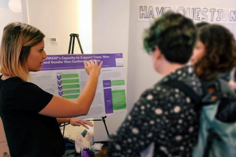 Courtney Roark discusses their poster with colleagues.