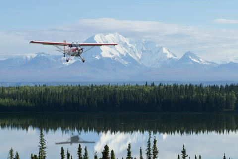 Photograph of small airplane flying over a lake with mountains in the background.