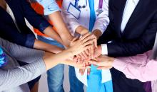 Photograph of a circle of people clasping hands in the middle of the group.