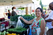 Photograph of a woman holding a bag of produce at a farmers market stall.