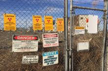 Photograph of a chain link fence with many warning signs posted on it.