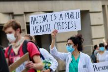 "woman holding ""racism is a public health crisis"" sign"