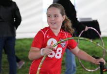 Photograph of a girl using a hula hoop wearing the Sqord bracelet.