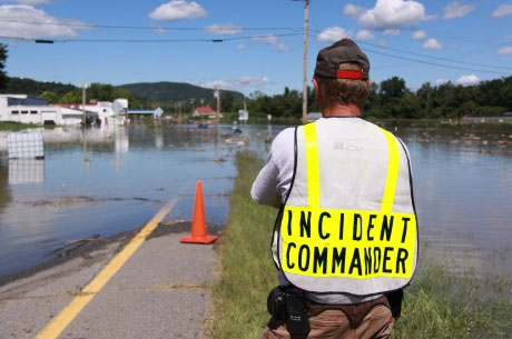 Photograph of a man in a vest reading Incident Commander looking at a flooded road.