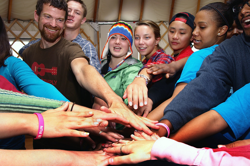 Photograph of several teens clasping hands in the center of a circle.