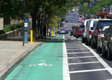 Photograph of a bicycle lane between a sidewalk and car traffic lanes.