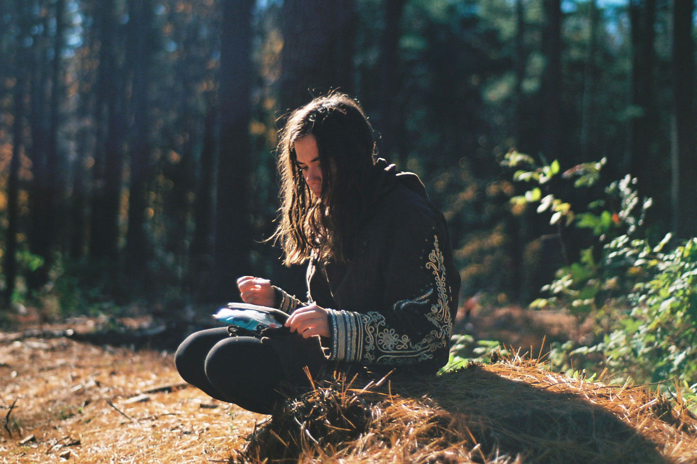 Photograph of a teen seated at the edge of a treed area.