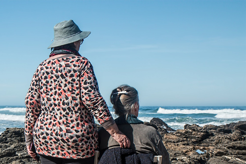 Photograph of two women looking at ocean waves.