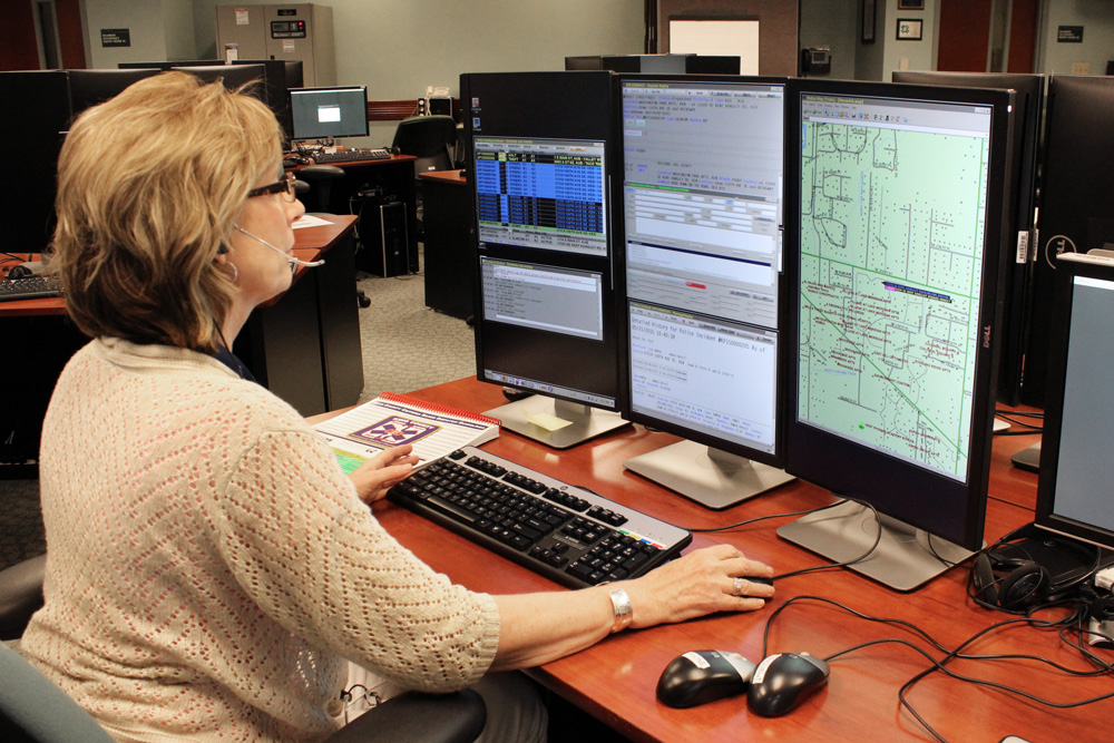 A 9-1-1 telecommunicator at her workstation.