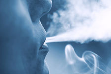 Photograph of a person's face breathing out vapor.