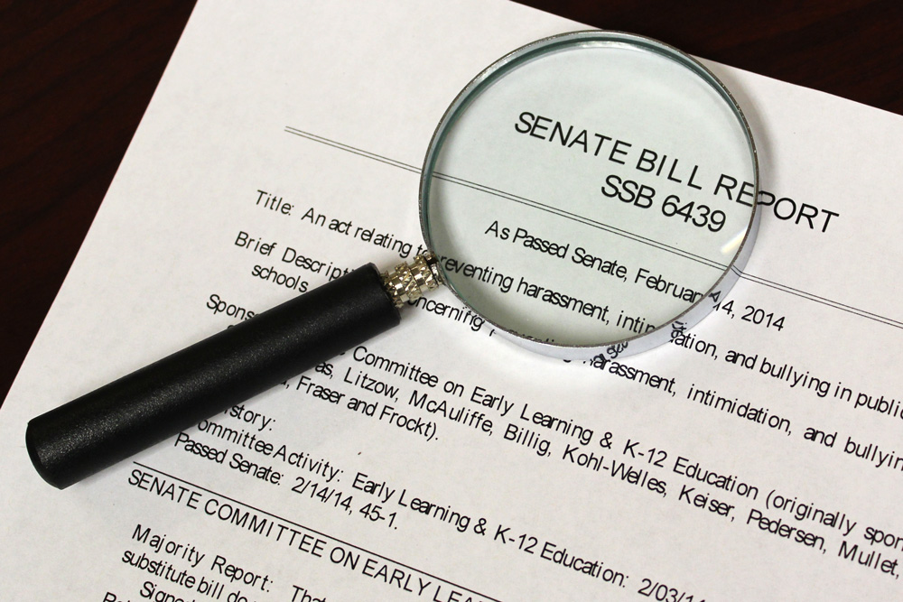 Photograph of a magnifying glass over a legal document.