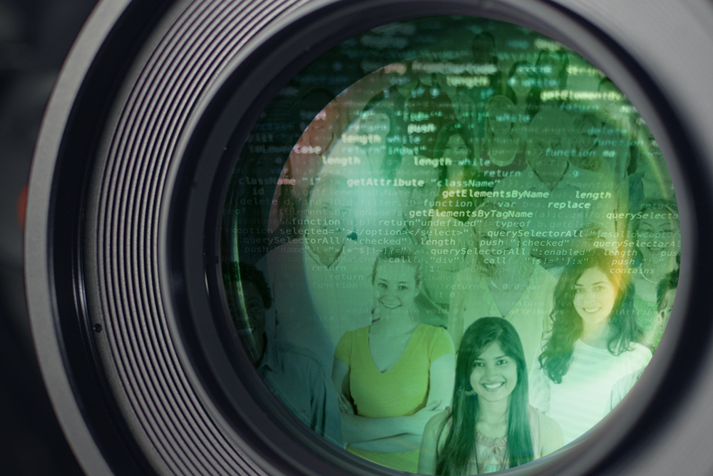 Close up view of green camera lens reflecting a crowd and computer code