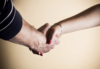Photograph of two hands clasped in a handshake.