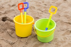 Photograph of two plastic buckets with plastic shovels side by side on a sandy beach.