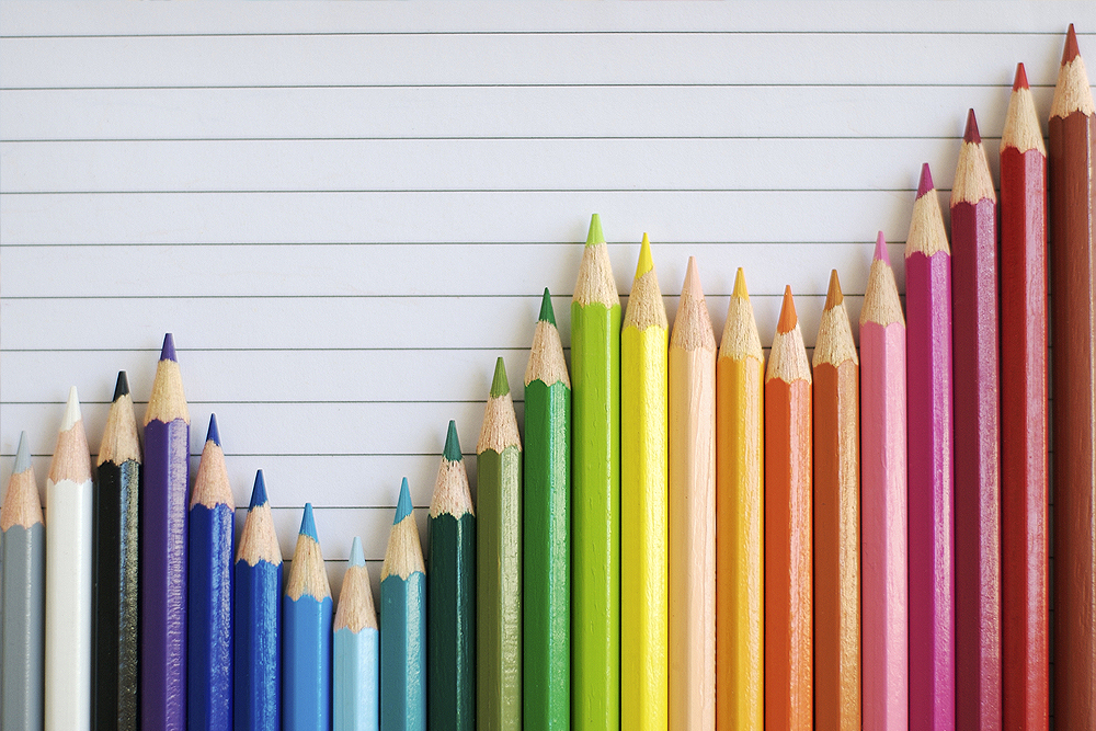 Photograph of a chart formed from a rainbow of colored pencils.