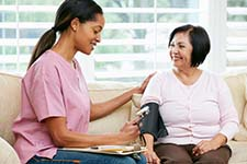 Photograph of a health care provider checking a client's blood pressure in a home setting.