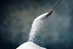 Photograph of a spoon pouring sugar onto a pile.