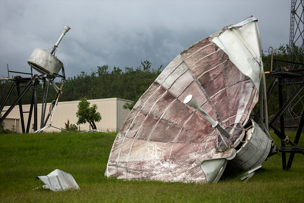 Photograph of satellite dish that has been destroyed by a storm.