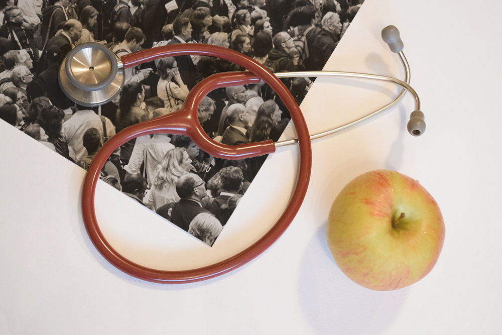 Photograph of a stethoscope and apple resting on a photo of a crowd of people.