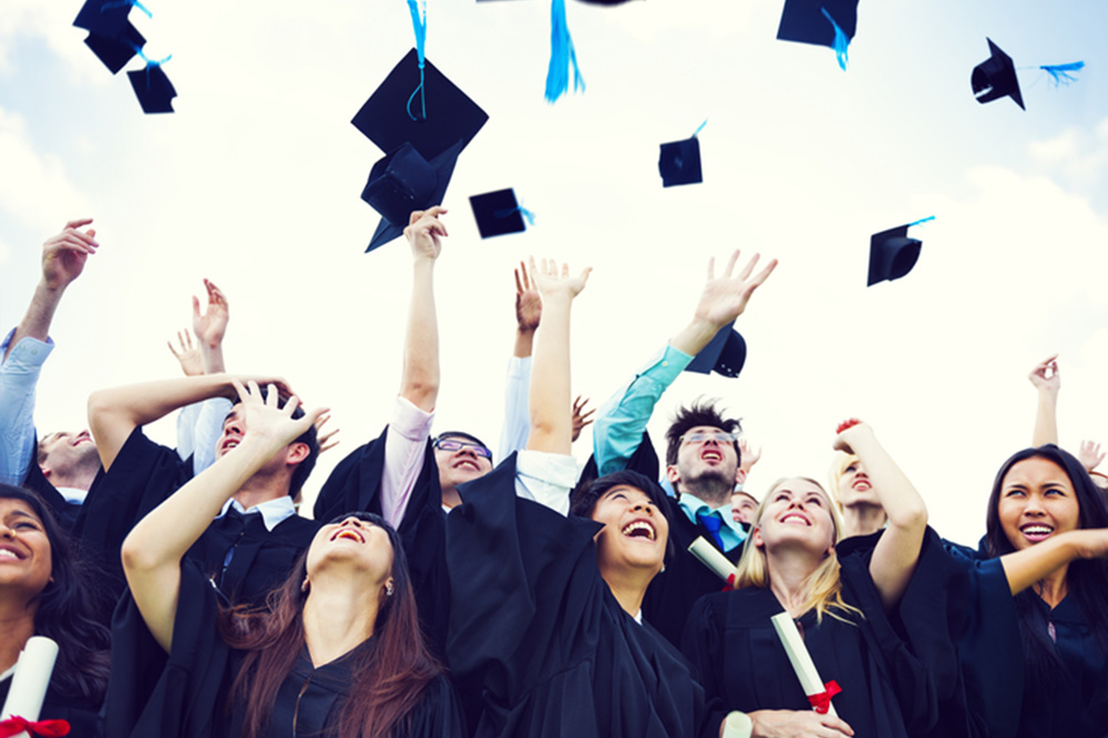 Photograph of graduates in regalia tossing their mortarboard hats.