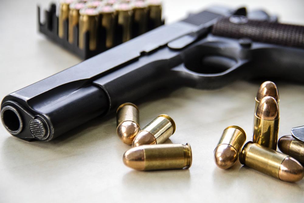 Photograph of a handgun and ammunition.