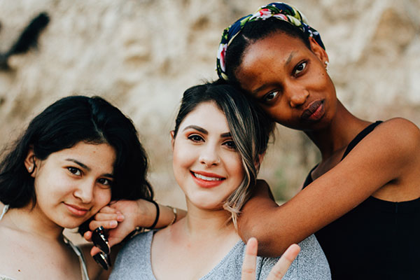 Photograph of three teens posing for a picture.