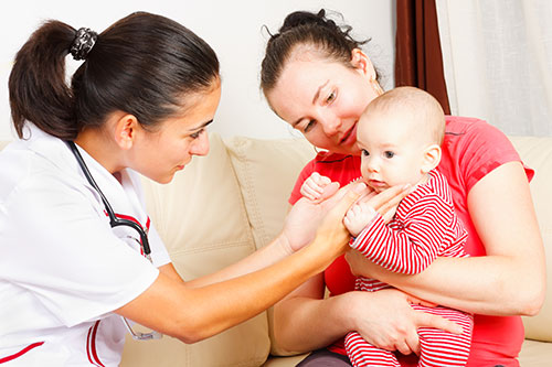Photograph of a woman and child consulting with a healthcare provider.