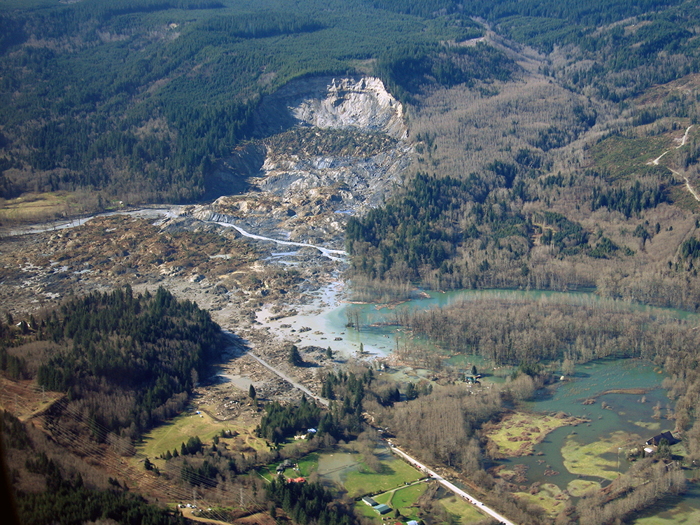 Photograph of Oso slide showing a large area of hillside has slid into the river valley.
