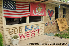 "Photograph of a boarded up house with an American flag and ""God Bless West"" painted on it."