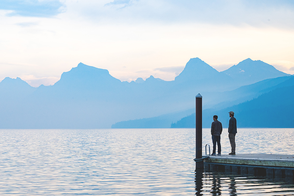 Photograph of two people on the end of a dock seen from a distance.