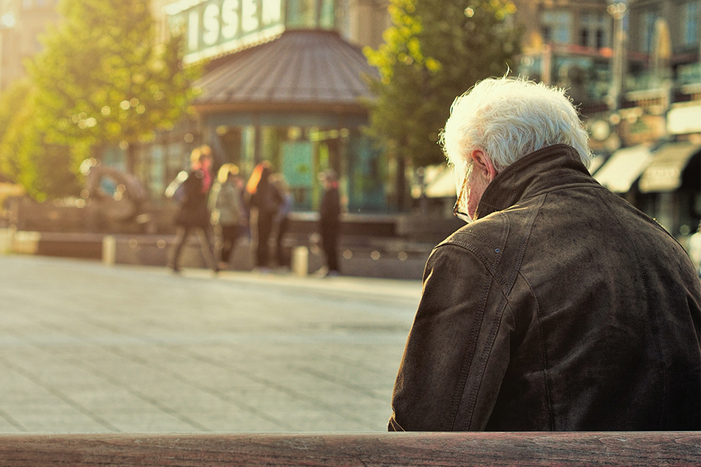 Elderly person looking down with back turned to camera