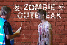 "Photograph of exercise staff with made-up actor superimposed over a ""zombie outbreak"" sign."