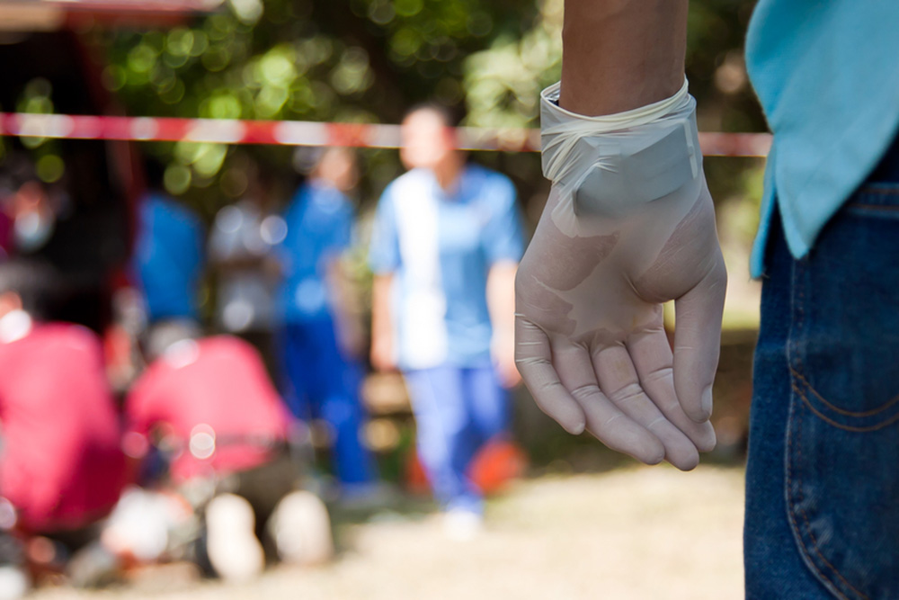 Photograph of a man's gloved hand with EMTs working in the background.