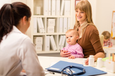 Photograph of women with small child and a medical provider.